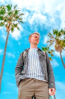 デニムジャケットを着た若い男がロサンゼルスのベニスビーチで青い空とヤシの木に立っています