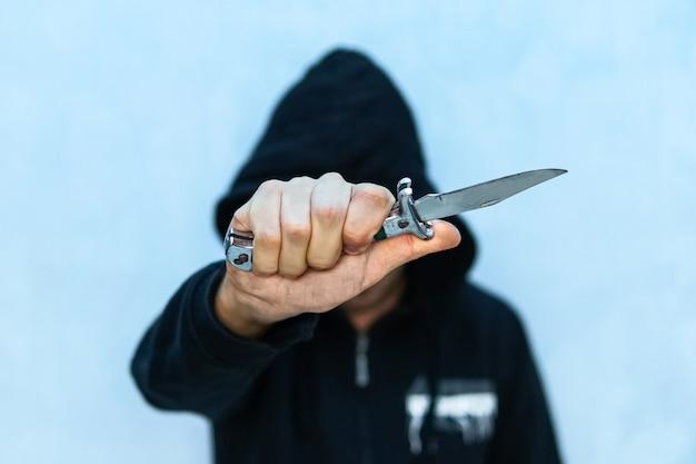 Молодой человек в толстовке с капюшоном держит нож, символизирующий преступление среди молодежи. понятие преступления. угроза холодного оружия. террорист из игил с ножом. заключенный с шивом.