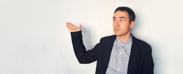 Молодой человек в куртке указывает на пустую синюю стену. мокап для дизайна. презентационный дисплей. пустой