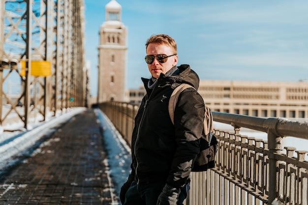 ジャケットを着た若い男が晴れた冬のサンクトペテルブルクのスノーブリッジを歩く