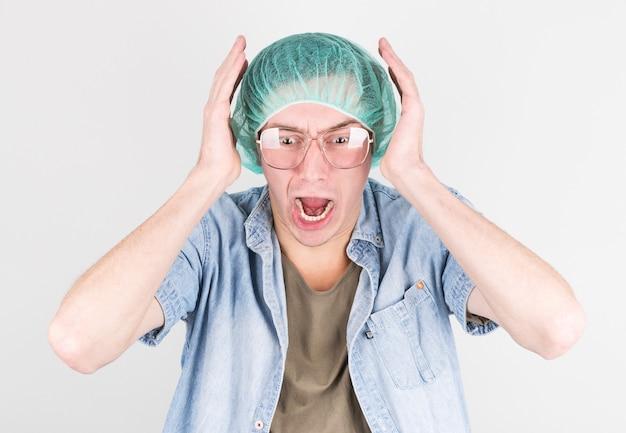 医療用の帽子と眼鏡をかけた若い男性が、灰色の壁で出産中に恐怖で悲鳴を上げます。出産プロセスの概念。