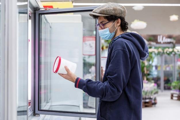 Молодой человек в медицинской маске выбирает замороженные продукты в супермаркете