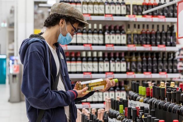 Молодой человек в медицинской маске выбирает вино в супермаркете