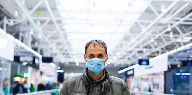 ショッピングセンターの医療マスクの若い男。仮面の男は、中国のウイルス「2019-nkov」の流行から身を守ります