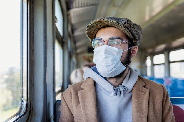 기차에서 의료 마스크에 젊은 남자. 코로나 바이러스 전염병 예방 조치.