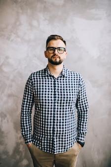격자 무늬 셔츠와 안경에 젊은 남자가 카메라에 포즈