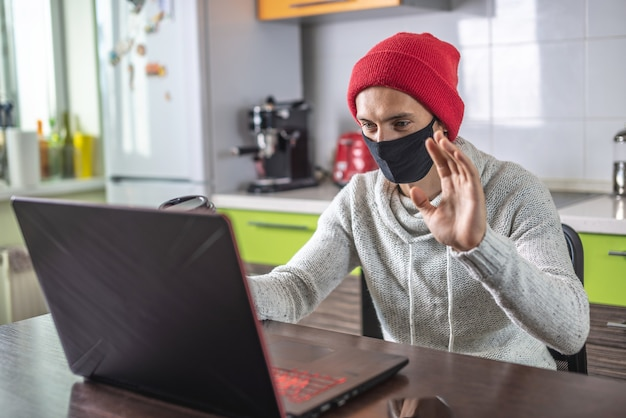 Молодой человек в защитной маске смотрит на экран ноутбука и машет рукой