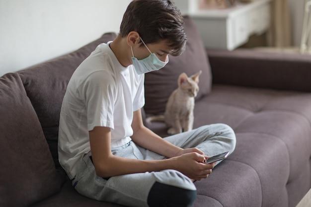 顔に防護マスクをした若者、手に電話、子猫が近くに座っている