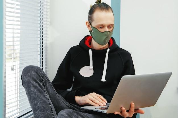 보호 마스크의 젊은 남자가 창에 앉아 컴퓨터에서 작동합니다. 코로나 바이러스, 집에서 격리 된 상태로 일합니다.