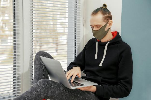 보호 마스크에 젊은 남자가 창문에 앉아 컴퓨터에서 작동 프리미엄 사진