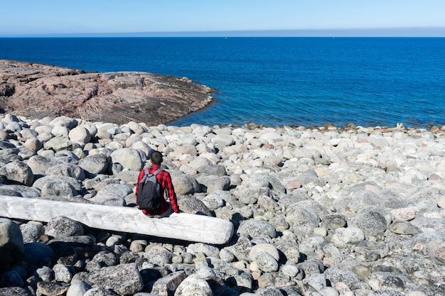 Молодой человек в красной клетчатой рубашке сидит один на бревне на берегу моря.