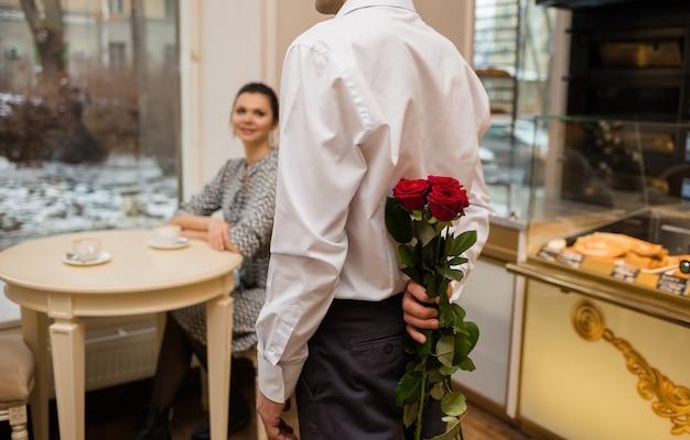 シャツを着た若い男が背中の後ろにバラの花束を持っています。カフェでデート