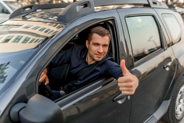 Молодой человек в рубашке сидит в своей машине и показывает большой палец вверх. таксист смотрит в камеру и улыбается. городская среда и движение