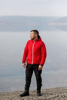 スポーツスーツを着た若い男が川のそばに立っている