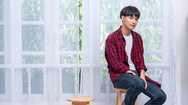 縞模様のシャツを着た若い男が高い椅子に座っています。