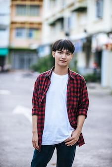 На улице стоит молодой человек в полосатой рубашке.