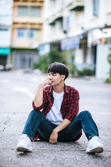 Молодой человек в полосатой рубашке сидит на улице