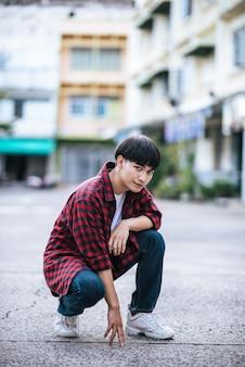 通りに座っている縞模様のシャツを着た若い男