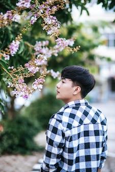 На обочине дороги стоял молодой человек в полосатой рубашке и держал цветок.