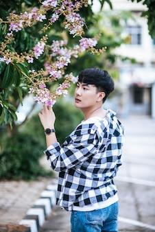 縞模様のシャツを着た若い男が道端に立っていて、花を持っていました。