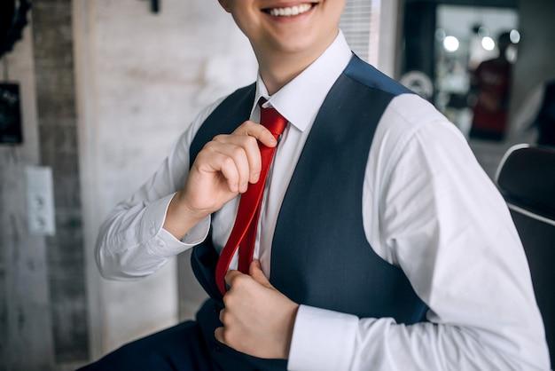 Молодой человек в костюме поправляет красный галстук, улыбаясь