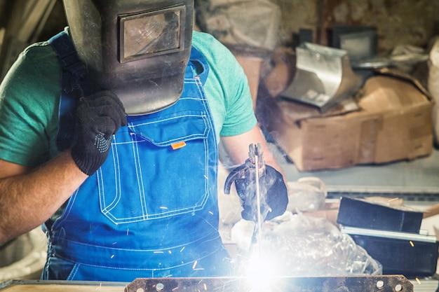 溶接マスクを着た若い男が、木製のテーブルの上で溶接機で金属を溶接している