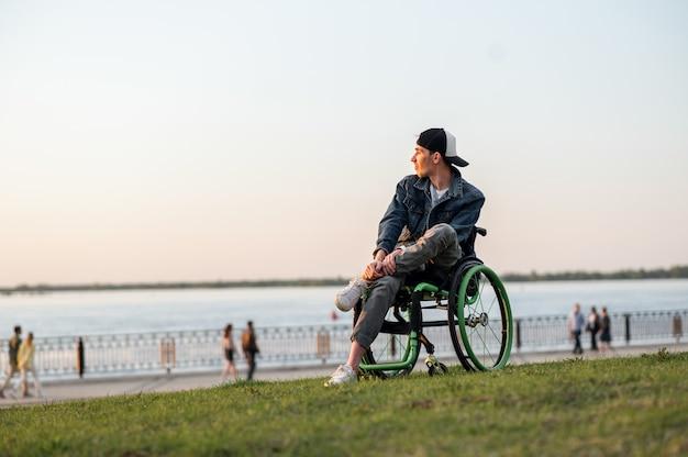 夕日の高品質の写真を楽しんで街を歩いている車椅子の若い男