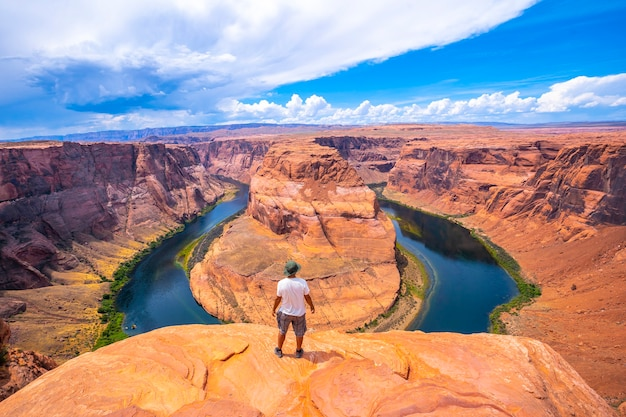 Молодой человек в белой рубашке и зеленой шляпе у хорсшу-бенд и реки колорадо на заднем плане, аризона. соединенные штаты