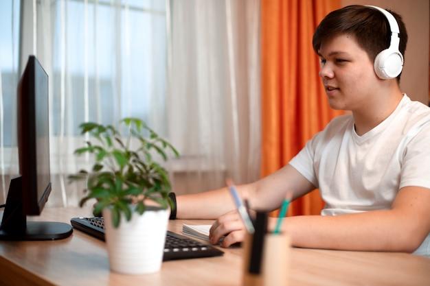 Молодой человек в белой футболке и наушниках сидит за столом и смотрит на монитор компьютера.