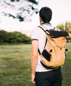 Молодой человек в белой футболке и шортах с бежевым и черным рюкзаком на плече стоит и смотрит вдаль. зеленое поле и чистое небо.