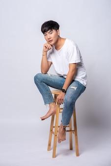 白いtシャツを着た若い男性が高い椅子に座っています。