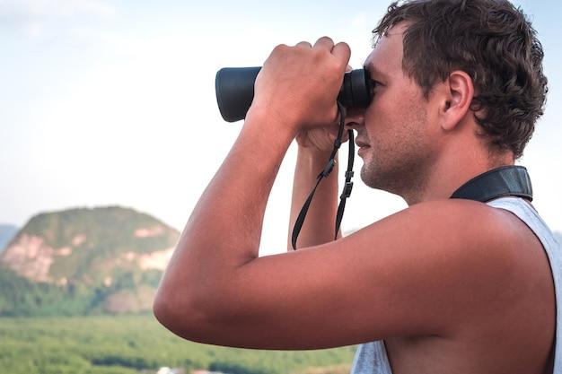 白いtシャツを着た若い男が、空と山のクローズアップを背景に双眼鏡で上から遠くを見ています。