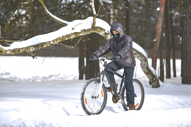 黒い服を着た若い男が雪の中で自転車に乗る