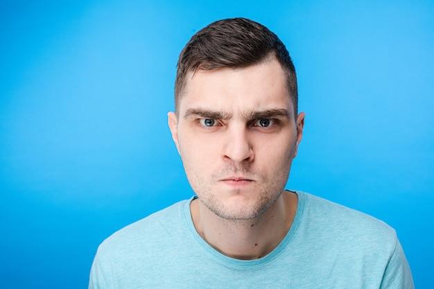 Молодой человек в синей футболке злится