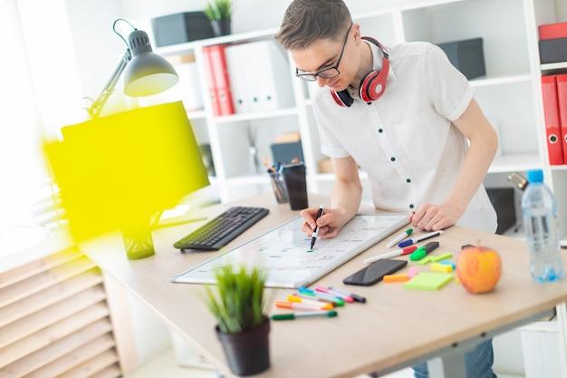 Молодой человек в очках стоит возле компьютерного стола. молодой человек рисует маркер на магнитной доске. на шее у парня висят наушники.