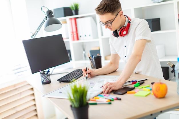 안경에있는 젊은이 컴퓨터 책상 근처에 서있다. 한 젊은 남자가 자기 보드에 마커를 그립니다. 목에 남자의 헤드폰이 걸려요.
