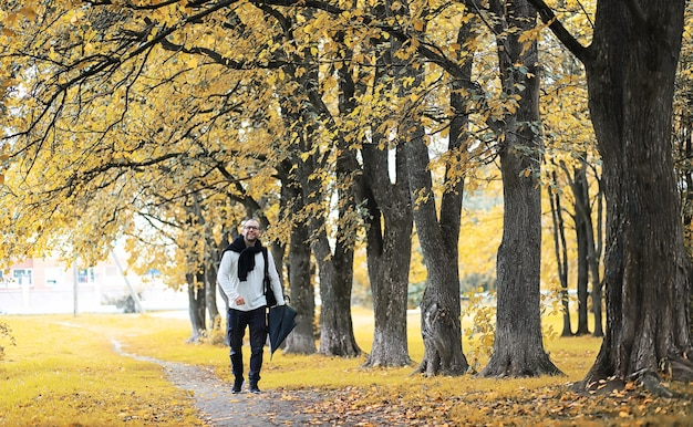 안경을 쓴 젊은 남자가 비가 오는 동안 우산을 들고 공원을 걷습니다.