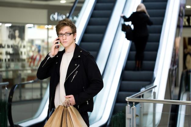 Молодой человек в очках с бумажные пакеты покупки в торговом центре и разговаривает по телефону.