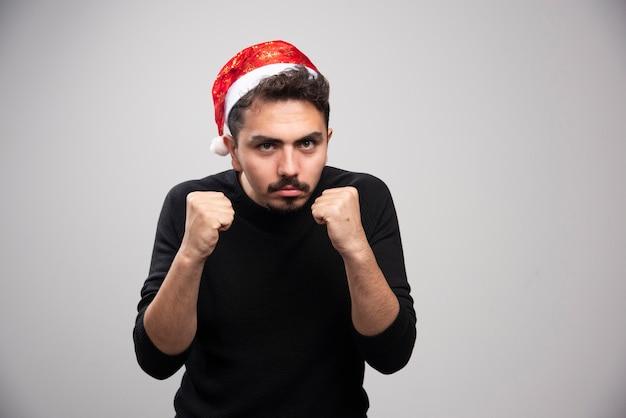 그의 주먹을 보여주는 산타 클로스 빨간 모자에서 젊은 남자.