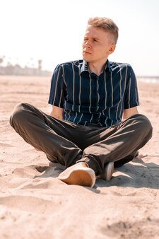 Молодой человек в рубашке отдыхает на песке пляжа в лос-анджелесе концепция летних каникул