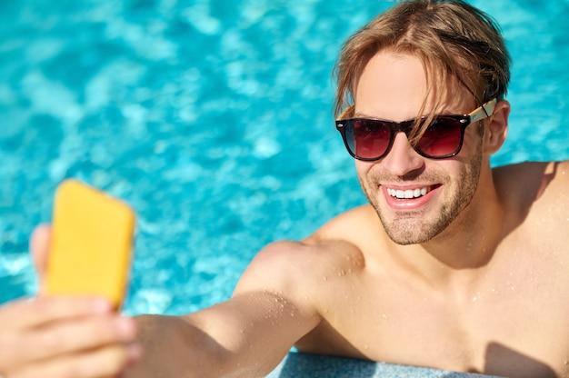Молодой человек в солнцезащитных очках делает селфи и улыбается