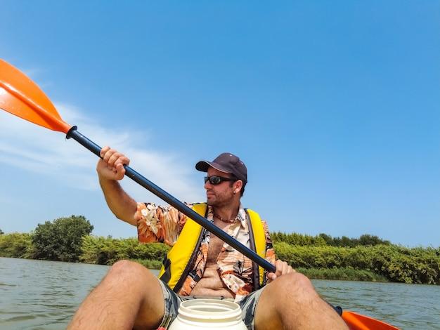 Молодой человек каноэ плывет на каноэ в природном парке каталонии, река рядом с пляжем в эстартите.