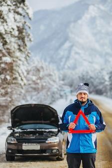 Молодой человек в горах держит за собой аварийный знак - разбитая машина