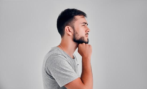 스튜디오에 있는 한 청년이 회색 배경을 생각하며 턱 아래에 주먹을 얹고 있다