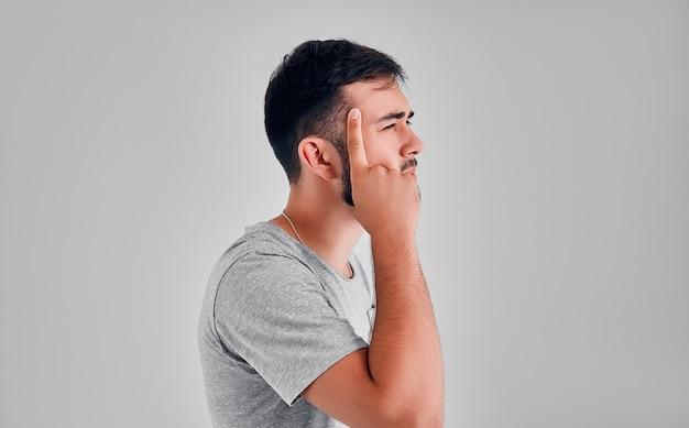 스튜디오에 있는 한 청년이 관자놀이에 손가락을 대고 회색 배경을 생각하고 있다