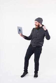 젊은 남자가 흰 벽 근처에서 자신의 컴퓨터를보고 매우 흥분되고 있습니다.