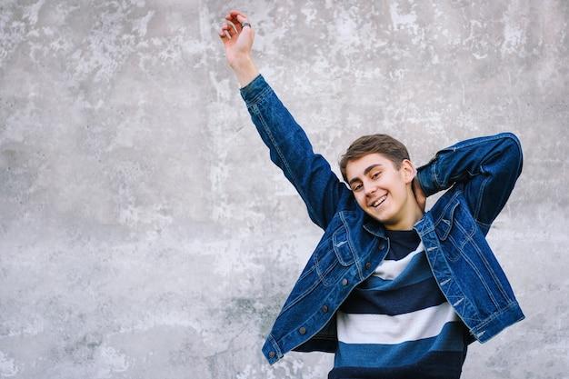 Молодой человек развлекается на бетонной стене в городе - подросток делает жест рукой
