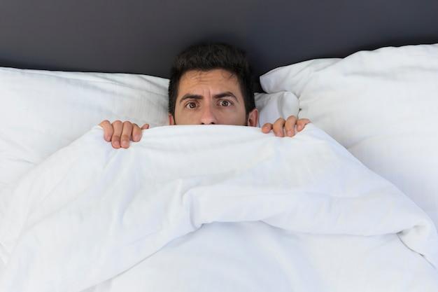 Молодой человек прячется в постели под одеялом у себя дома. страх и удивление видны в его глазах.