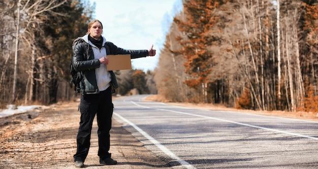 Молодой человек путешествует автостопом по стране. мужчина пытается поймать проезжающую машину для путешествия. мужчина с рюкзаком отправился автостопом на юг.