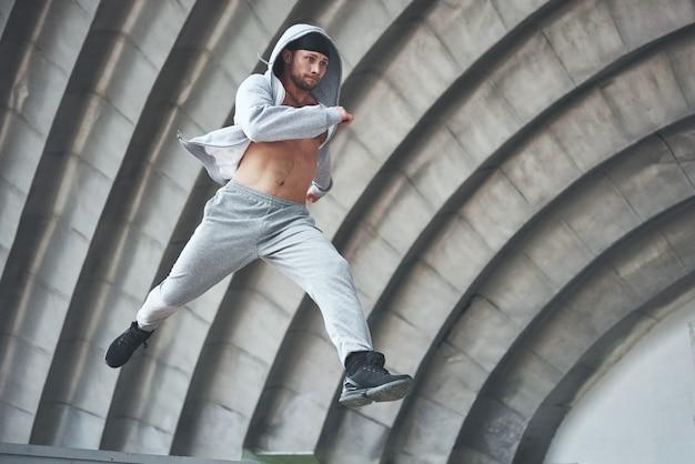 若い男がジャンプしています。都市空間のパルクール、スポーツ活動。